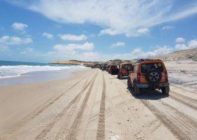 carros jimny em linha na praia